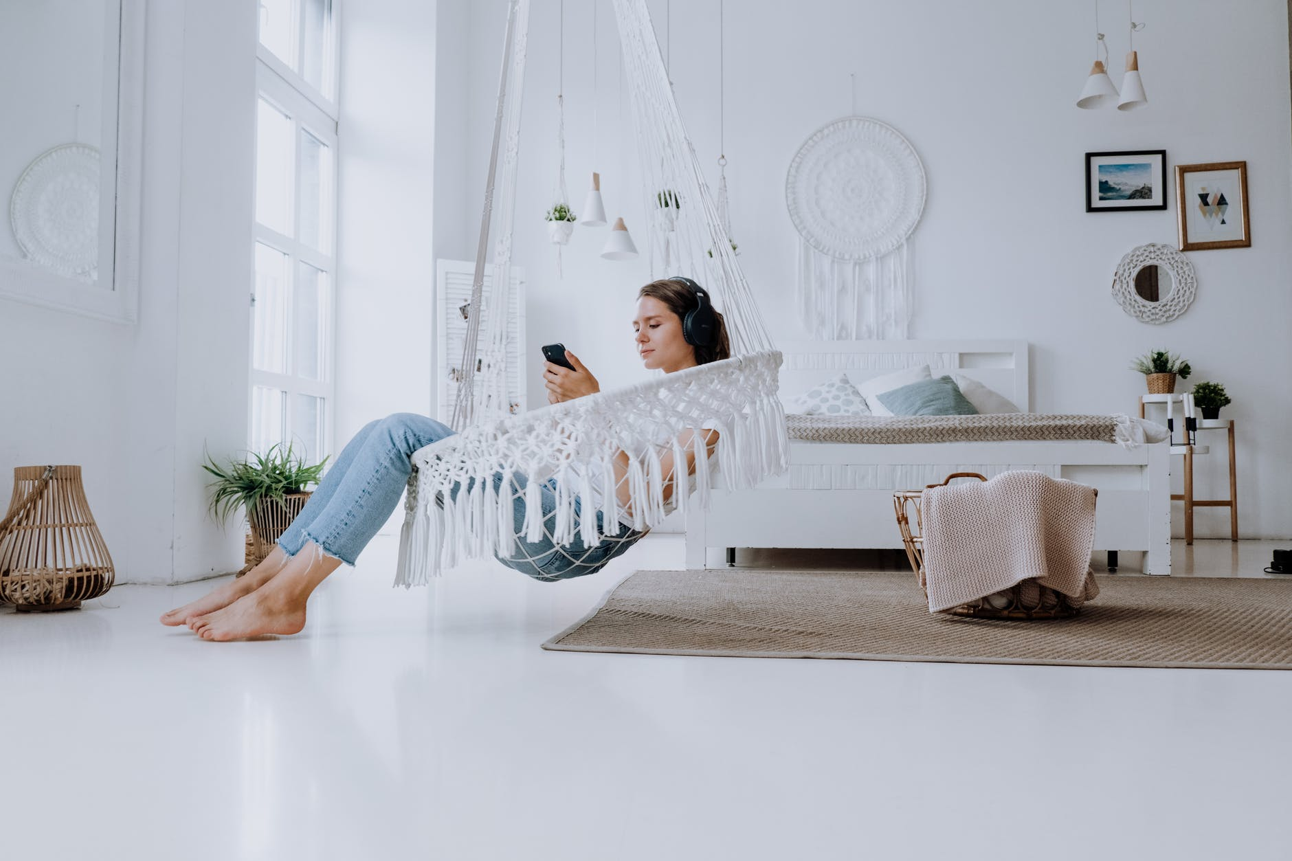 woman in white and blue long sleeve shirt and blue denim jeans lying on white bed
